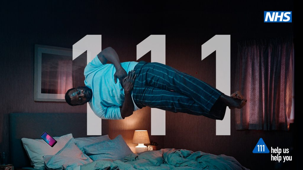 NHS 111 image of a man holding his stomach in bed