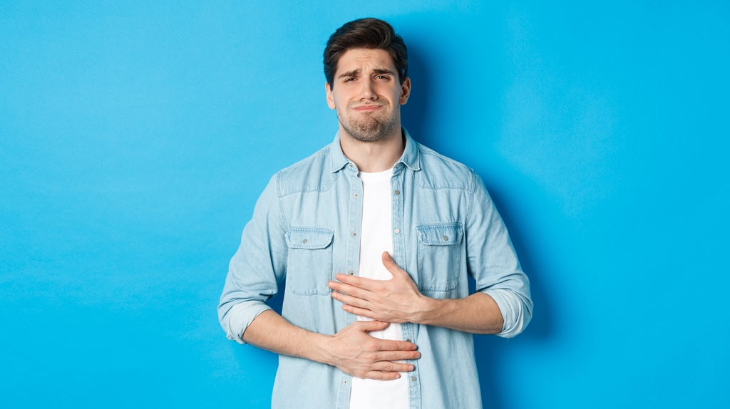 man-holding-hands-belly-grimacing-from-pain-complaining-stomach-ache-standing-against-blue-background